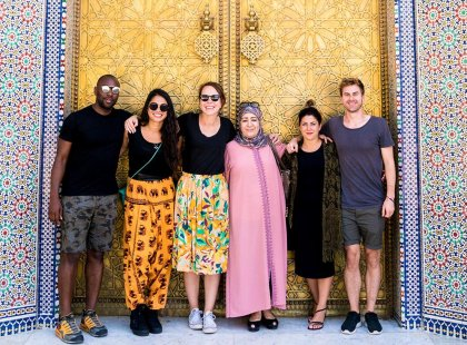 Intrepid Travel group and local woman standing in colourful doorway, Fes, Morocco