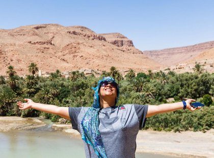 Happy traveller spreading arms, Todra Gorge, Morocco