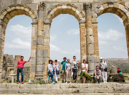 Intrepid Travel group posing under arch, Voulibis ruins, Morocco
