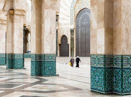 Local women walking through archways of Hassan II Mosque, Casablanca, Morocco