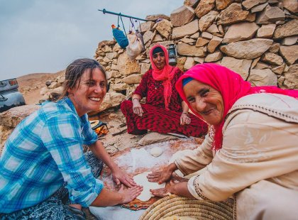 Traveller and local berber woman preparing food at Sahara desert camp, Morocco