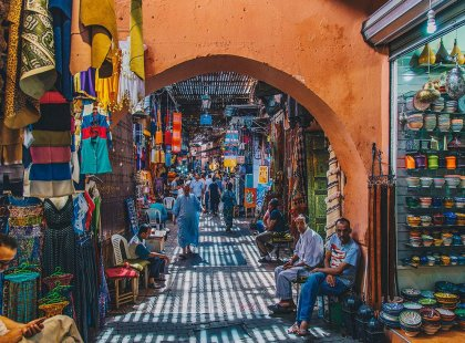 Locals sitting in colourful market medina, Marrakech, Morocco