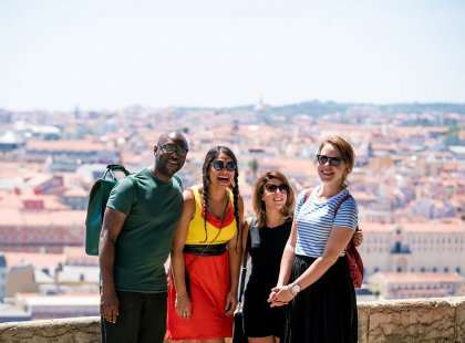Group of Intrepid travellers laughing with city view in Lisbon, Portugal
