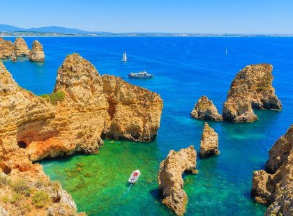 Scenic view of boats between rocks and ocean, The Algarve, Portugal