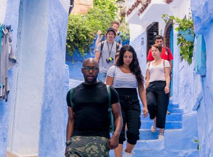 Intrepid Travel group walking down stairs in blue streets of Chefchaouen, Morocco