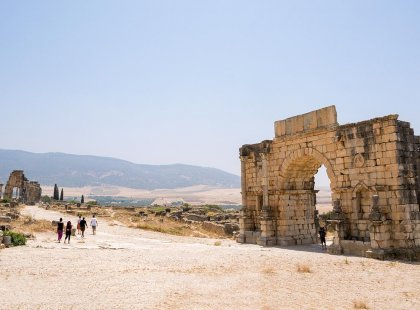 Travellers walking landscape of Volubilis ruins, Morocco