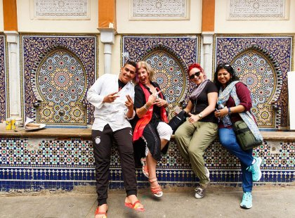 Intrepid Travel group posing in front of mosaic building, Rabat, Morocco