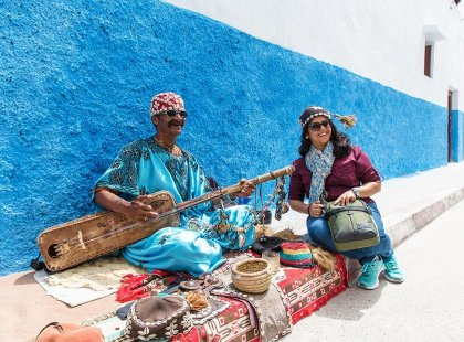 Traveller with local musician on blue street, Rabat, Morocco