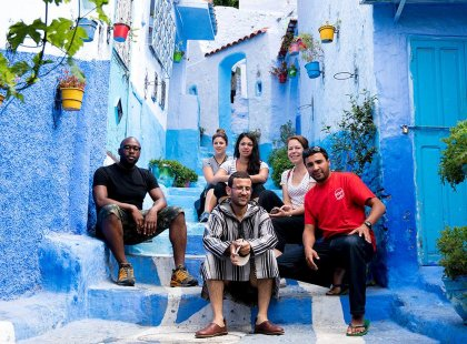 Intrepid Travel group sitting on stairs in blue streets of Chefchaouen, Morocco