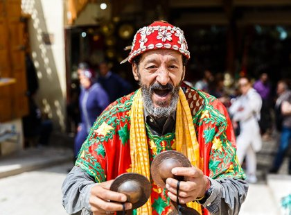 Local man in colourful traditional dress plays music, Fes, Morocco