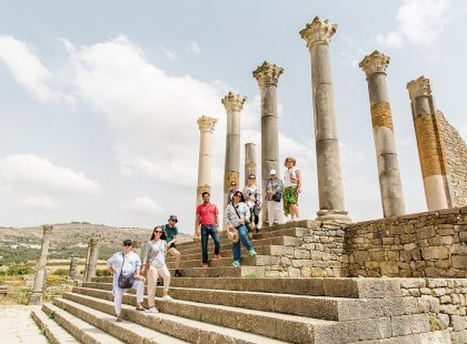 Intrepid Travel group posing with pillars of ruins in Voulibis, Morocco