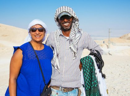 Traveller with local bedouin smiling in desert, Israel & the Palestinian Territories