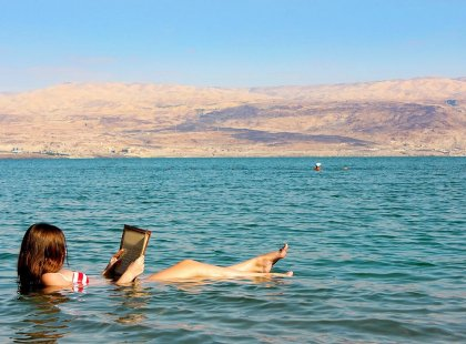 Woman reading book and floating in the Dead Sea, Israel & the Palestinian Territories