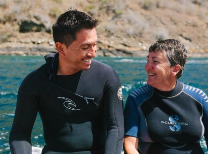 Man and woman smiling in wetsuits, snorkelling in the Galapagos Island
