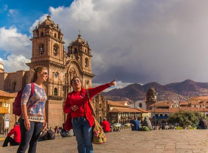 Traveller and tour leader in front of Cathedral, Plaza De Arma, Cusco, Peru
