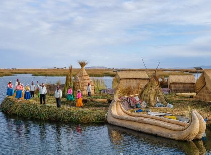 Locals waving welcome on floating island, Lake Titicaca, Peru