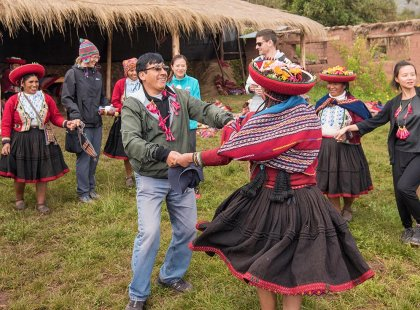 Group of travellers and locals dancing in traditional dress, Sacred Valley community visit, Peru