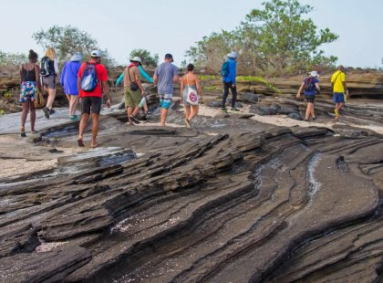 Group walking over volcanic lava formations, Galapagos Islands